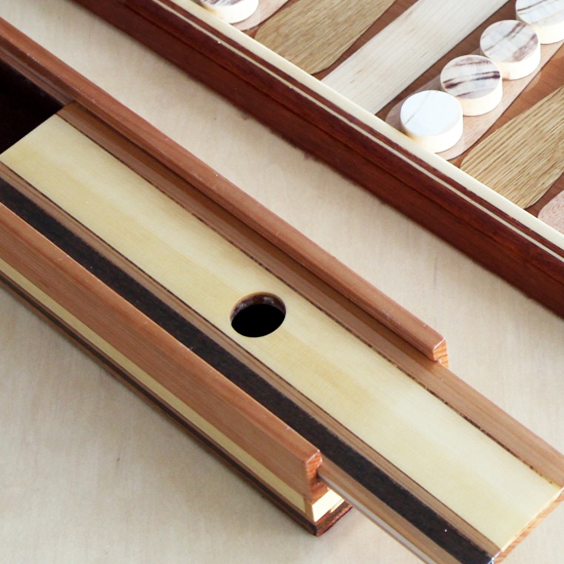 Playing checker and dice box; highly crafted in mahogany and insets of maple and Brazilian ipe, with a sliding cover