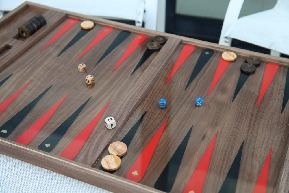 This classy board is made of richly colored solid walnut. As the original piece was made for a resort in Nevada, I gave it a little wink and a smile with teardrop shaped points with playing card suits in hand applied gold leaf (which, by the way, represent wind, fire, water, earth)
