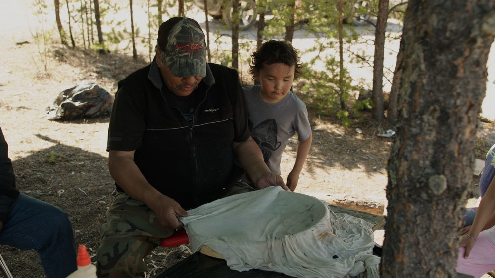 Elders from Black Lake, Saskatchewan teach the younger generation to make traditional drums out of stretched caribou hide.