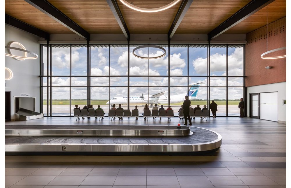 Brandon Municipal Airport, interior photo of arrivals hall wall of windows with people watching a plane taxi by / Photo:  Lindsay Reid