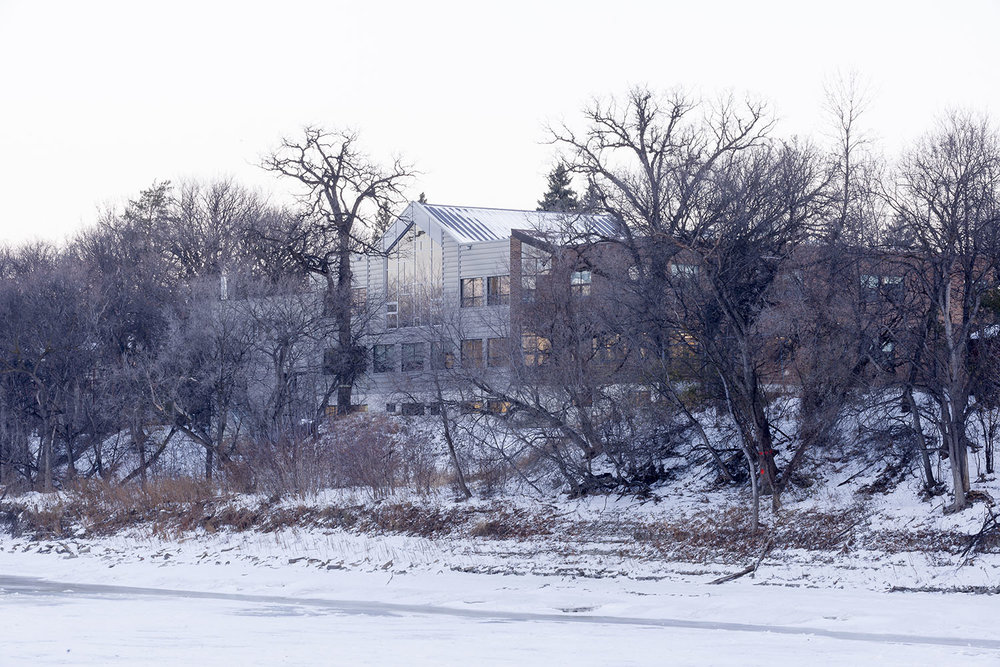 Westgate Mennonite Collegiate, exterior photo of building from across the river in winter