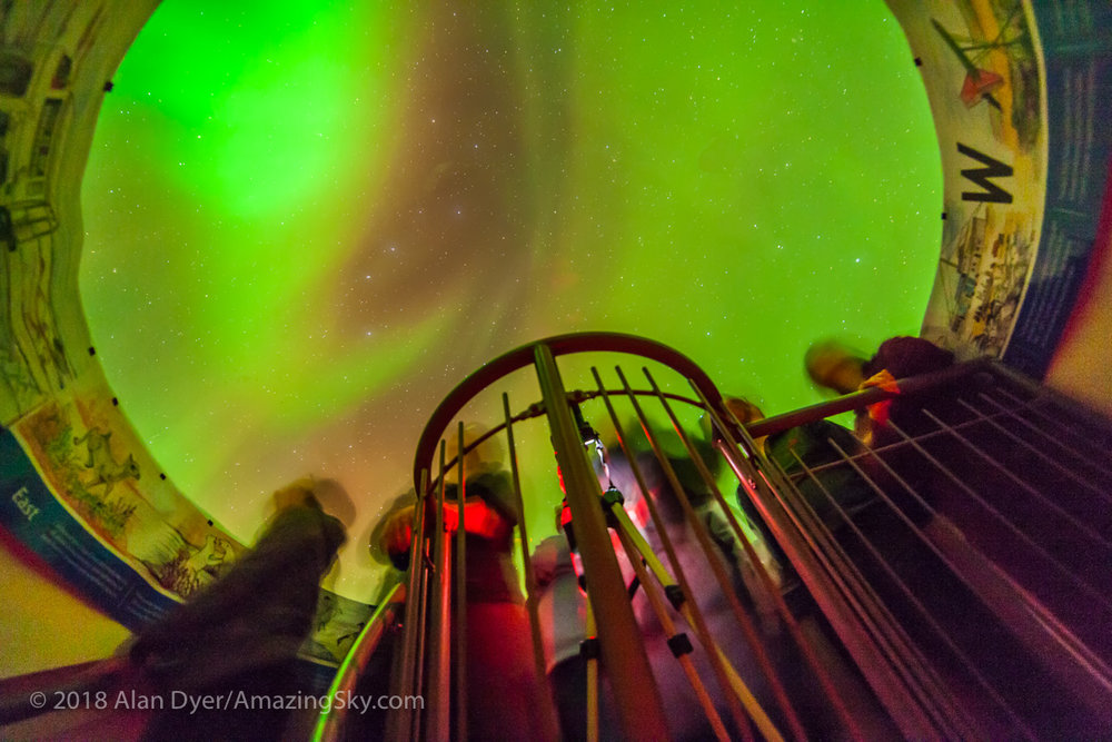 """The aurora of February 3-4, 2014 seen from Churchill, Manitoba at the Churchill Northern Studies Centre, in a view taken from inside the building looking up through the plexi """"aurora dome,"""" a warm way to watch the aurora. This is a 30-second exposure at f/2.8 with the 14mm lens and ISO 3200 wth the Canon 5D MkII."""