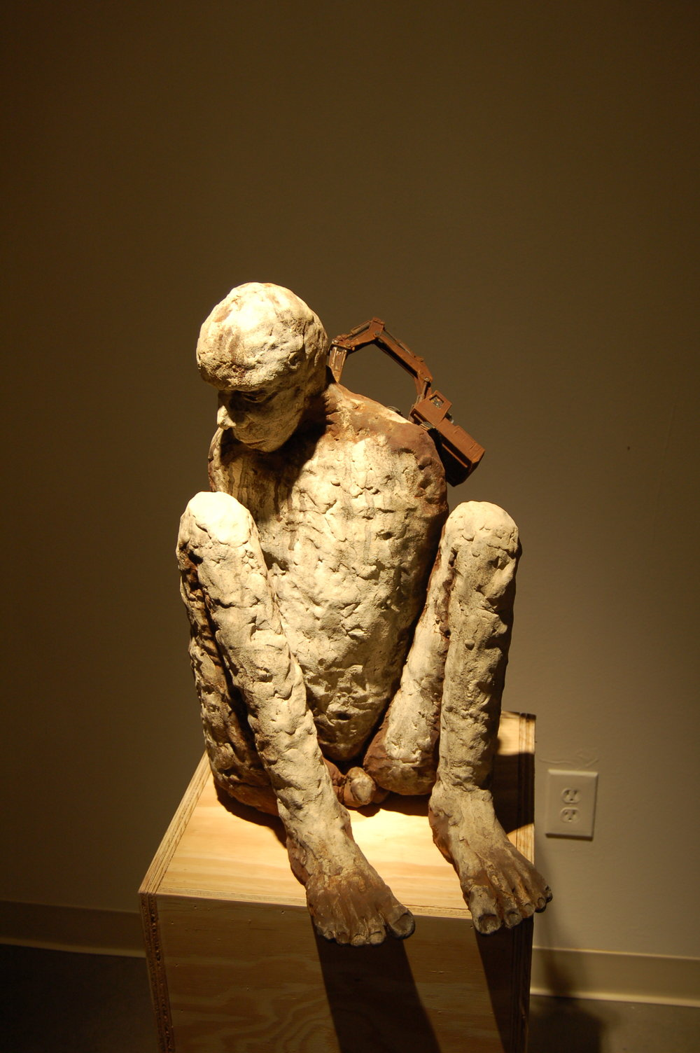 Excavating the present   2005  Ceramic with rusted toy  23 x 12 x 18   A toy machine penetrates the spine of the figure, creating a life of pain and limitations.     (my neck vertebrae C-7 was fractured in 1979)