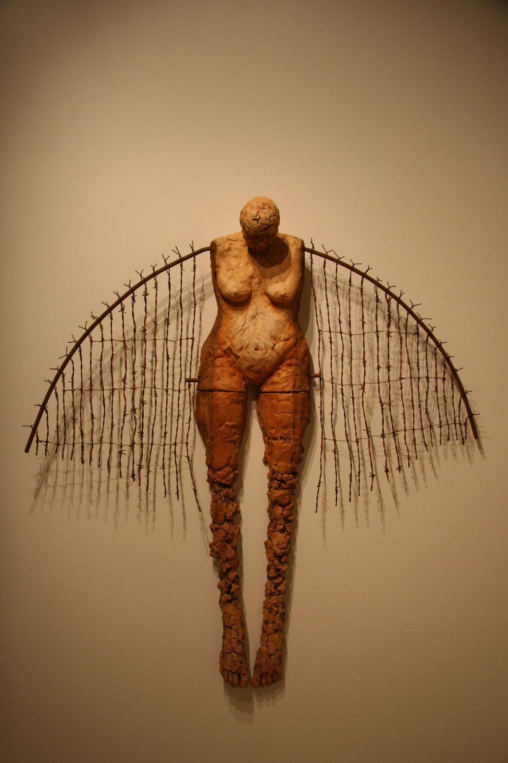 Gently and slowly rising   2001  Ceramic, steel & wire  60 x 53 x 8   The steel and barbed wire of our cages, when transformed into wings, becomes that which lifts us above the suffering and into a life of vital transcendence.