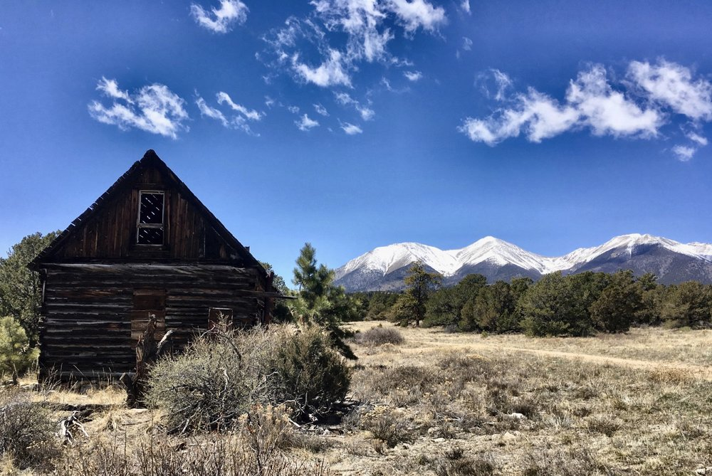 Snow-covered Shavano and Tabeguache rising behind an abandoned cabin. Photo: Greg Heil