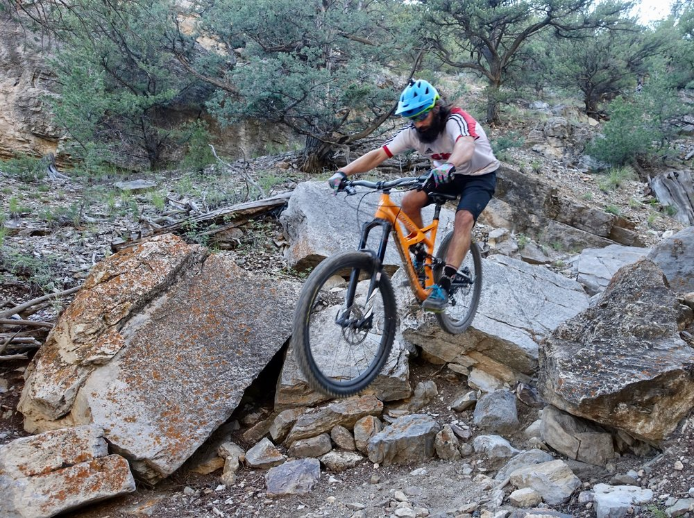 Airing off a drop in the technical Waterfall section of the Cottonwood trail. Rider: The Singletrack Sampler. Photo: Greg Heil.