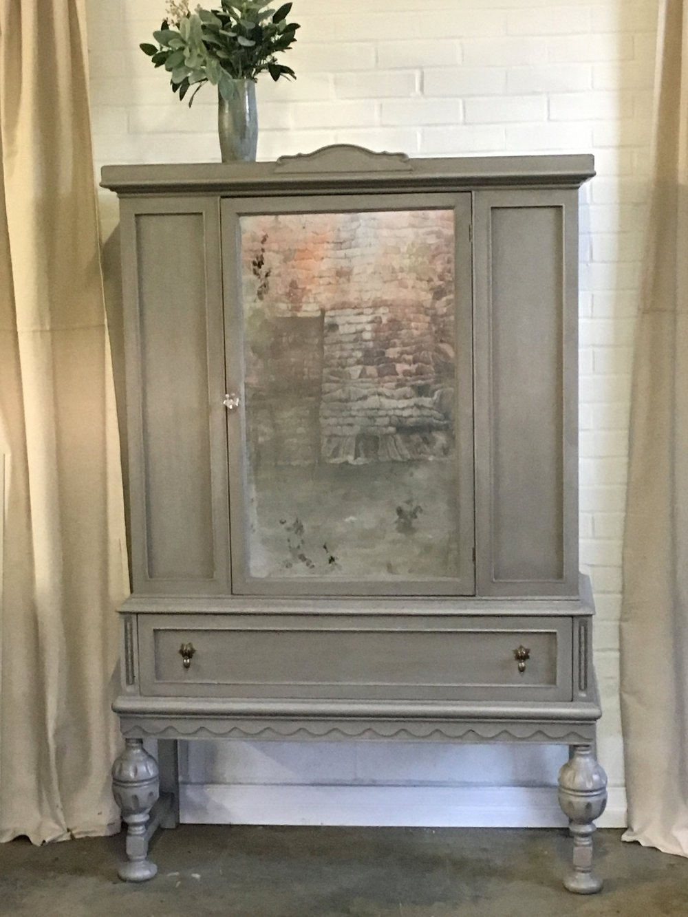 Beautiful cabinet for any room. Grey with slight distressing and antique mirror. $420 Available at The Blue Hearth