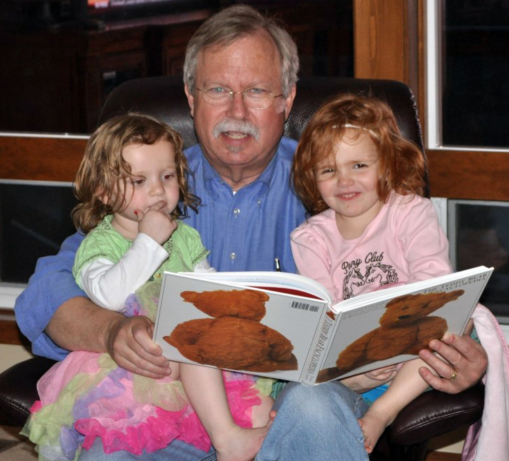 - Mike reading with his granddaughters a few years ago.