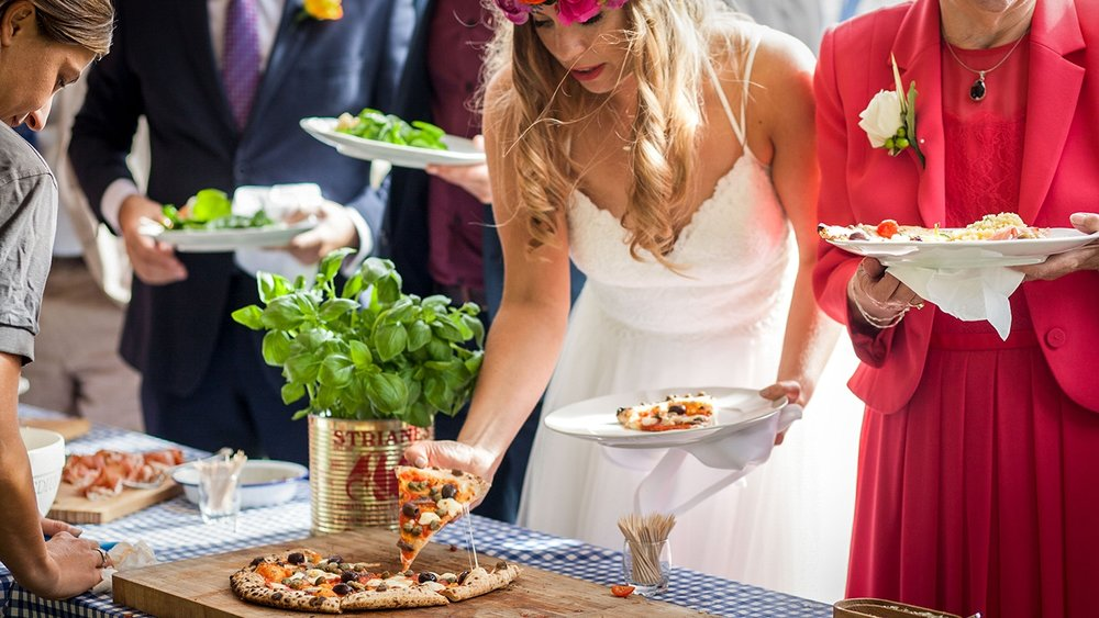 A wedding bride eating one of our wood fired pizzas. The Pizza Project provide pizza wedding catering