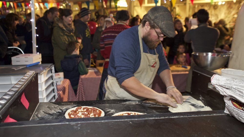 A pizza chef prepares wood fired pizzas for one of the pizza project's street food stalls.