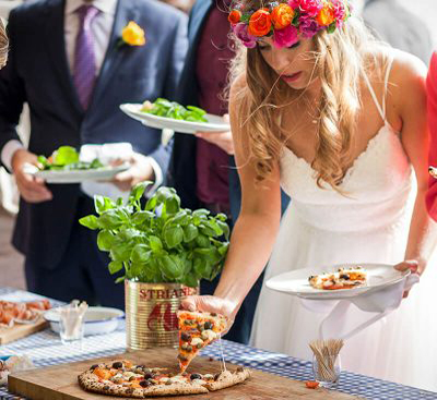 A wedding bride takes a slice of Pizza Project pizza from our wedding catering services.