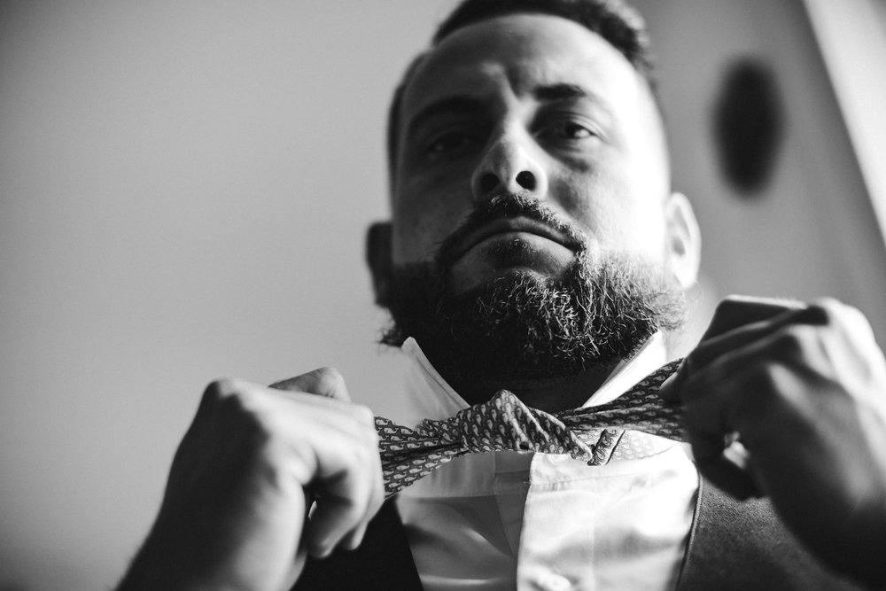 groom-tying-bow-tie-getting-ready-wedding-day-tiny-house-photo-florida-wedding-photographer.jpg