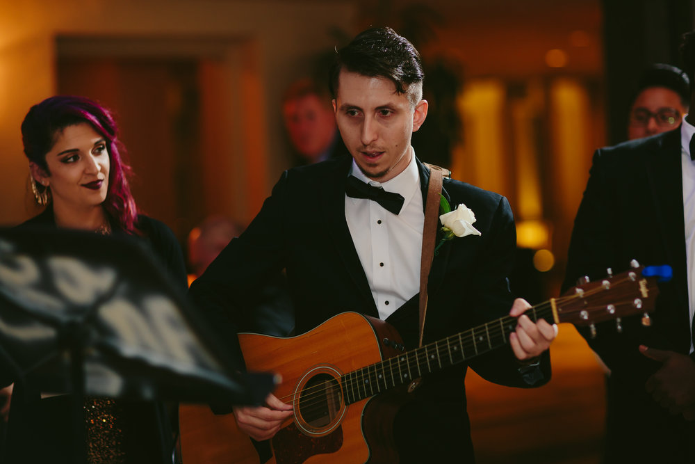 groomsman_singing_guitar_the_addison_wedding_moments_tiny-house_photo.jpg