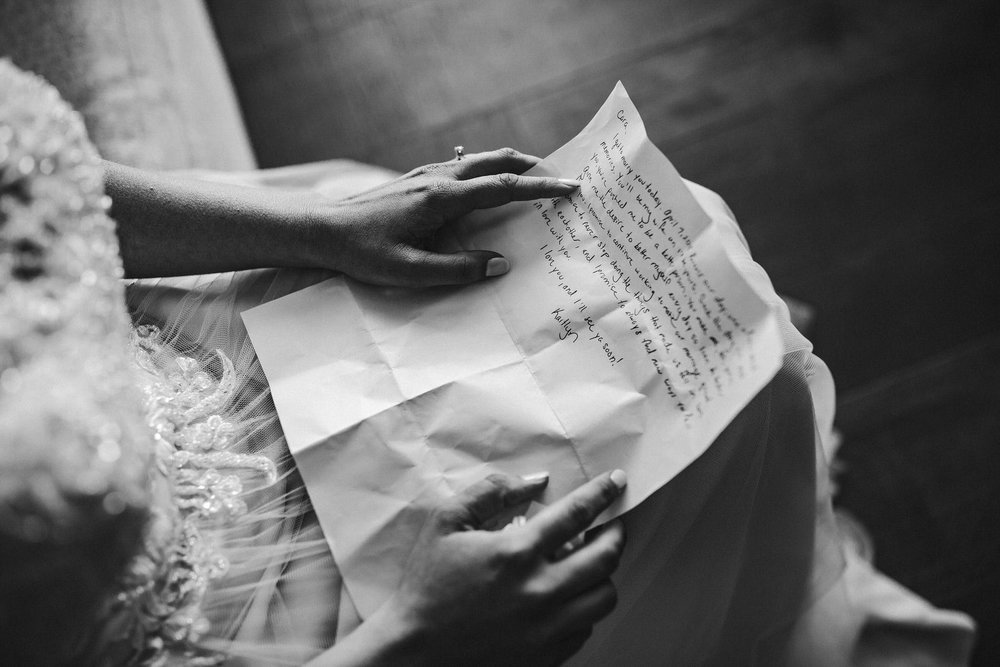 bride_hands_reading_letter_emotional_wedding_photography.jpg