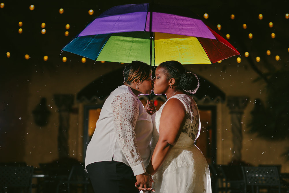 Same sex wedding brides kissing in the rain under a rainbow umbrella