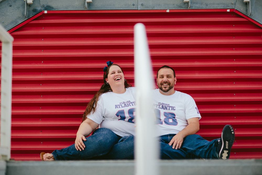 happy_laughing_couple_engagement_session_football_field_tiny_house_photo_boca_wedding_photographer.jpg