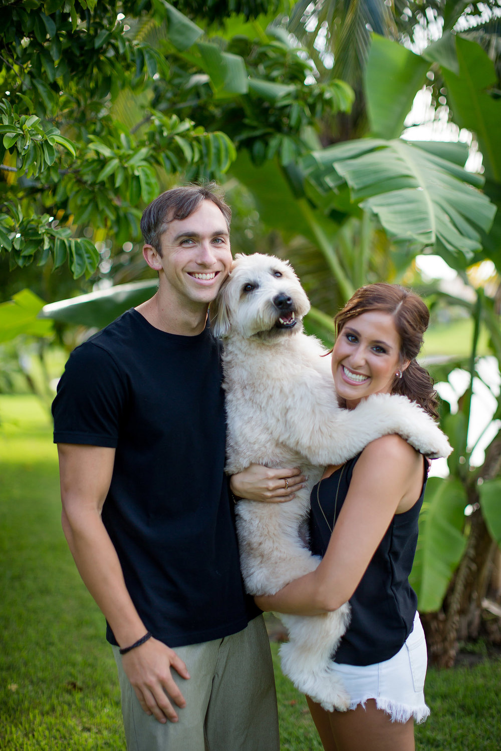 Adorable engaged couple holding their cute puppy
