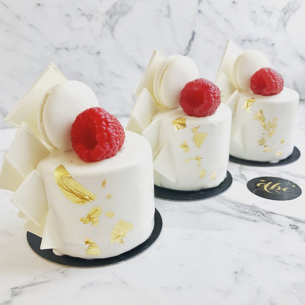 VANILLA BEAN CHEESECAKES  Biscuit base, vanilla bean cheesecake, white mirror glaze, vanilla macaron, white chocolate shards, fresh raspberry and edible gold leaf.  $7.90 each  Minimum Order Quantity : 8