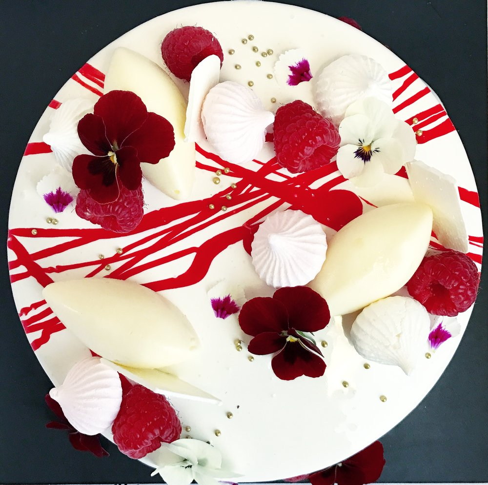 "RASPBERRY AND WHITE CHOCOLATE ENTREMET  Biscuit base, Vanilla Cheesecake, Raspberry Compote, White Chocolate Mirror Glaze, White Chocolate Mousse Quenelles, Fresh Raspberries, Meringue Kisses, White Chocolate Shards, Macarons, Edible Flowers.  6"" size $49.00 Feed upto 8  8"" size $69.00 Feed upto 12"