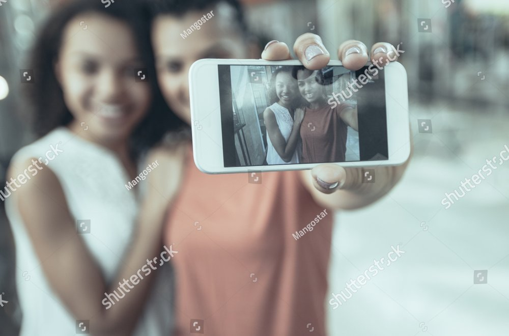 stock-photo-closeup-portrait-of-two-smiling-black-beautiful-girls-taking-selfie-photo-in-with-focus-on-1132451237.jpg