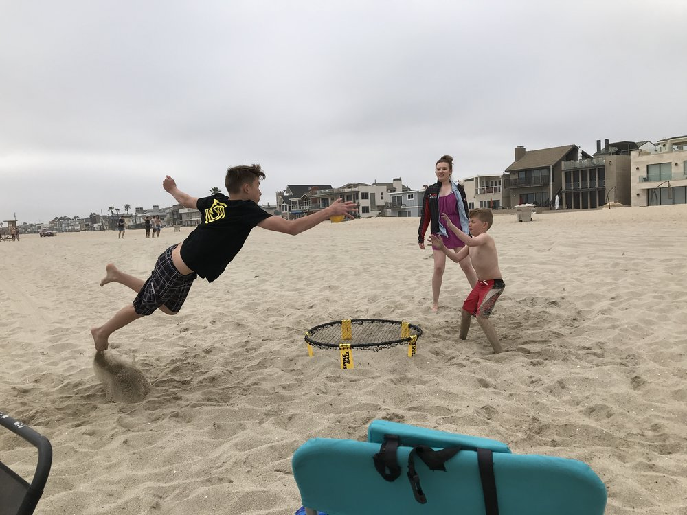 Nate playing on his newly won Spikeball net on the beach with his family.
