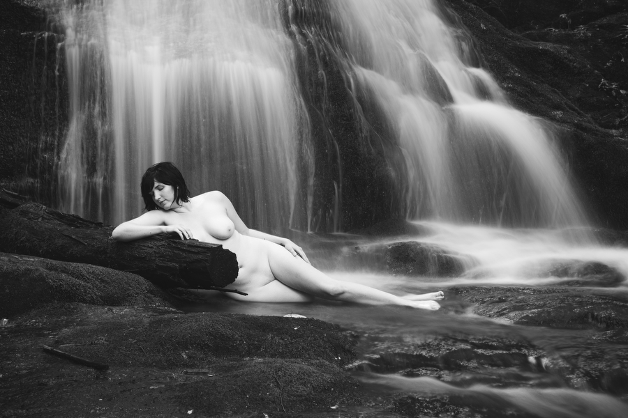 curvy fine art nude in nature by waterfall