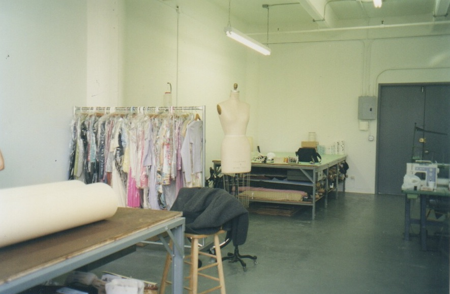 A designer's work space includes many cutting tables where patterns are cut and rolls of fabric are stored. Racks of samples and patterns, as well as rows of industrial sewing machines and steam irons, line the space. This is where the magic happens!