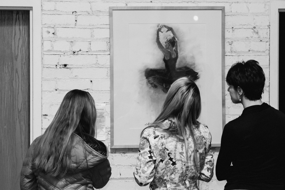 "Junction Box visitors viewing ""Death Spin,"" a charcoal drawing by Mitch Castor. Photo by  Amanda Tipton, 2014"