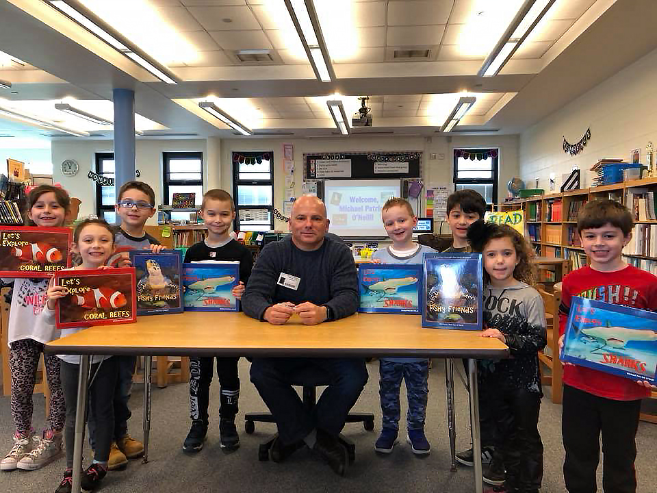 Children with their copies of Michael's educational books in a school in Manalapan, NJ in March 2018.