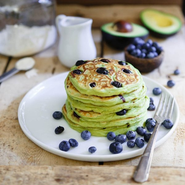 BLUEBERRY AVOCADO PANCAKES - 1 cup all-purpose flour (or a gluten-free blend)1 1/2 tablespoons sugar (any kind)1 teaspoon baking powder1/2 teaspoon salt1/4 teaspoon nutmeg1 ripe California avocado, mashed3/4 cup milk (dairy, nut milk, etc.)1 egg1 tablespoon melted coconut oil1/2 teaspoon vanilla extract1/2 cup blueberriesButter for the pan2 eggs, poached or friedSee it here