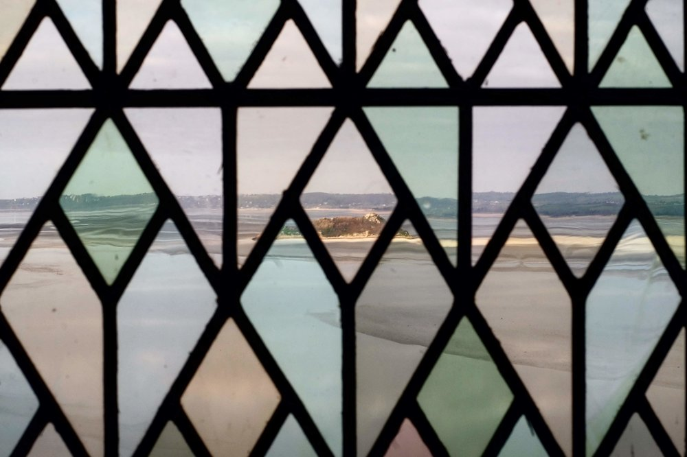 Views of the ocean through the stained glass windows of the abbey