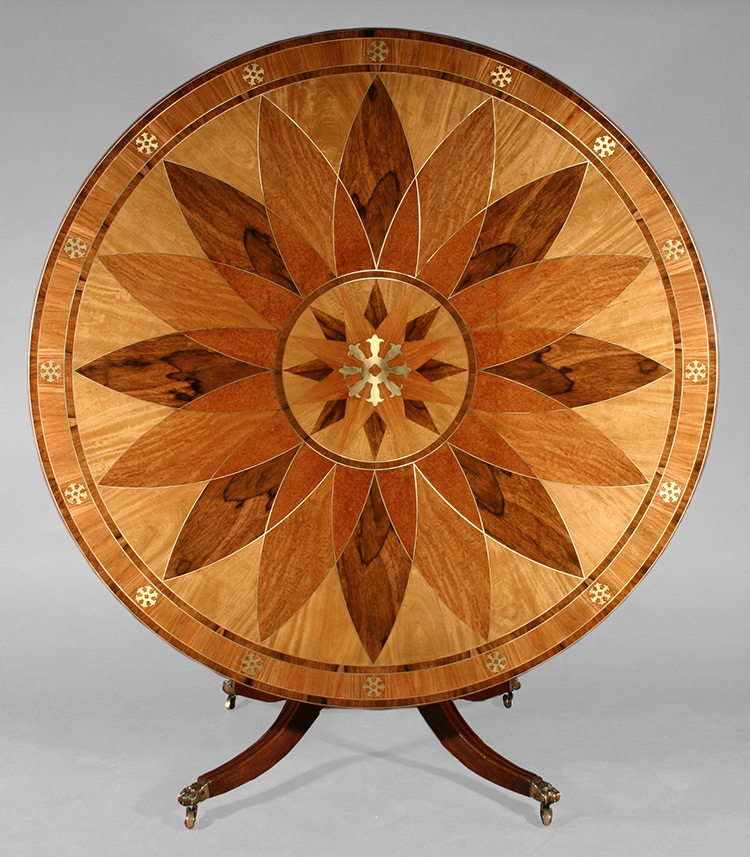 This rosewood marquetry table exemplifies many design elements of the Regency style, an English furniture style dominant between 1800 and 1830. The round table top is attached to a pedestal base supported by splayed legs terminating in lion's paw feet, all of which are characteristic of the Regency style. The brass inlay decoration was also a popular feature during this period. Symmetry was another important component of Regency design. Close examination of the inlaid decoration reveals the pieces of veneer used for the large dark petals were cut from the same piece of wood. The use of the nearly identical cuts of veneer placed opposite each other further demonstrates the importance of symmetry in the composition. The tilt-top table design allows the top to be tipped into a vertical position, either to save space or display the decorative design on the table top.   Read full story...