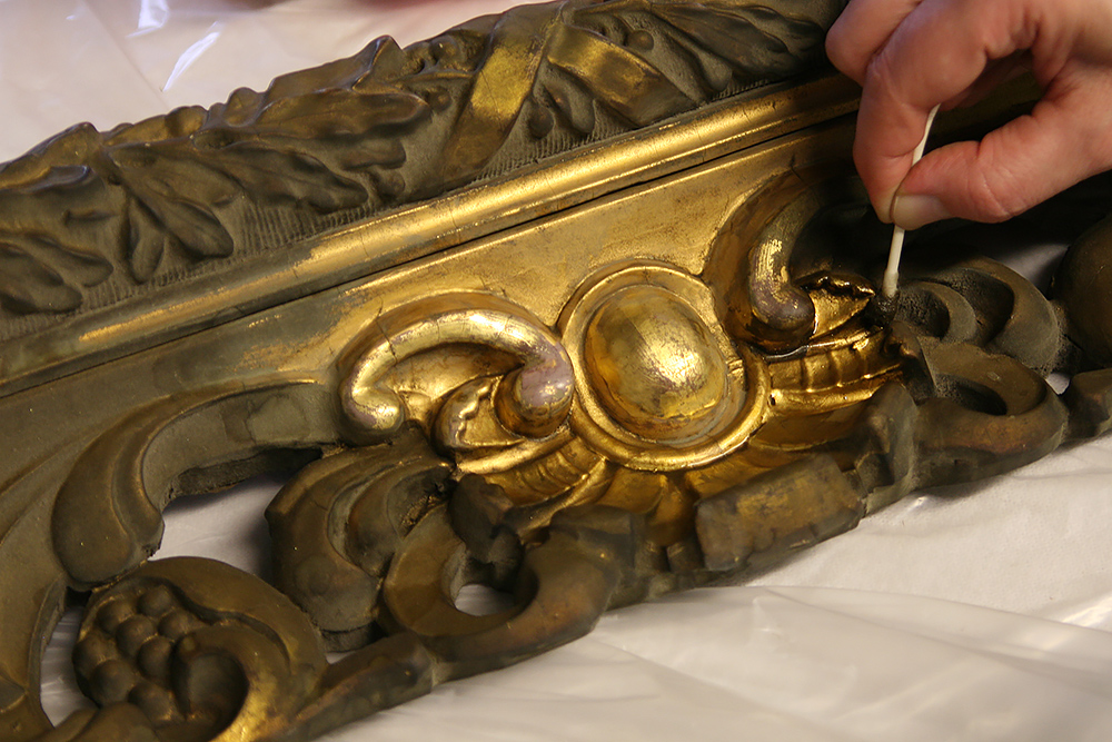 Conservation and restoration often means trying to fix previous incompetent and inappropriate repairs.  These are often much more difficult to repair than the original repairs would have been due to the introduction of incompatible coatings or adhesives that are very difficult to separate and remove from the original material. Sometimes you get lucky as we did recently with a gilded frame for a local client.  The carved wood frame came in completely covered with a bronze powder coating that seemed fairly recent though badly oxidized and was a dark green/brown. It was obvious that there were some losses of gesso on two of the corners but the rest of the carving seemed to be intact. Testing showed that the binder of the coating was nitrous- cellulose lacquer that broke down quickly with the introduction of lacquer thinner.   Read full story...
