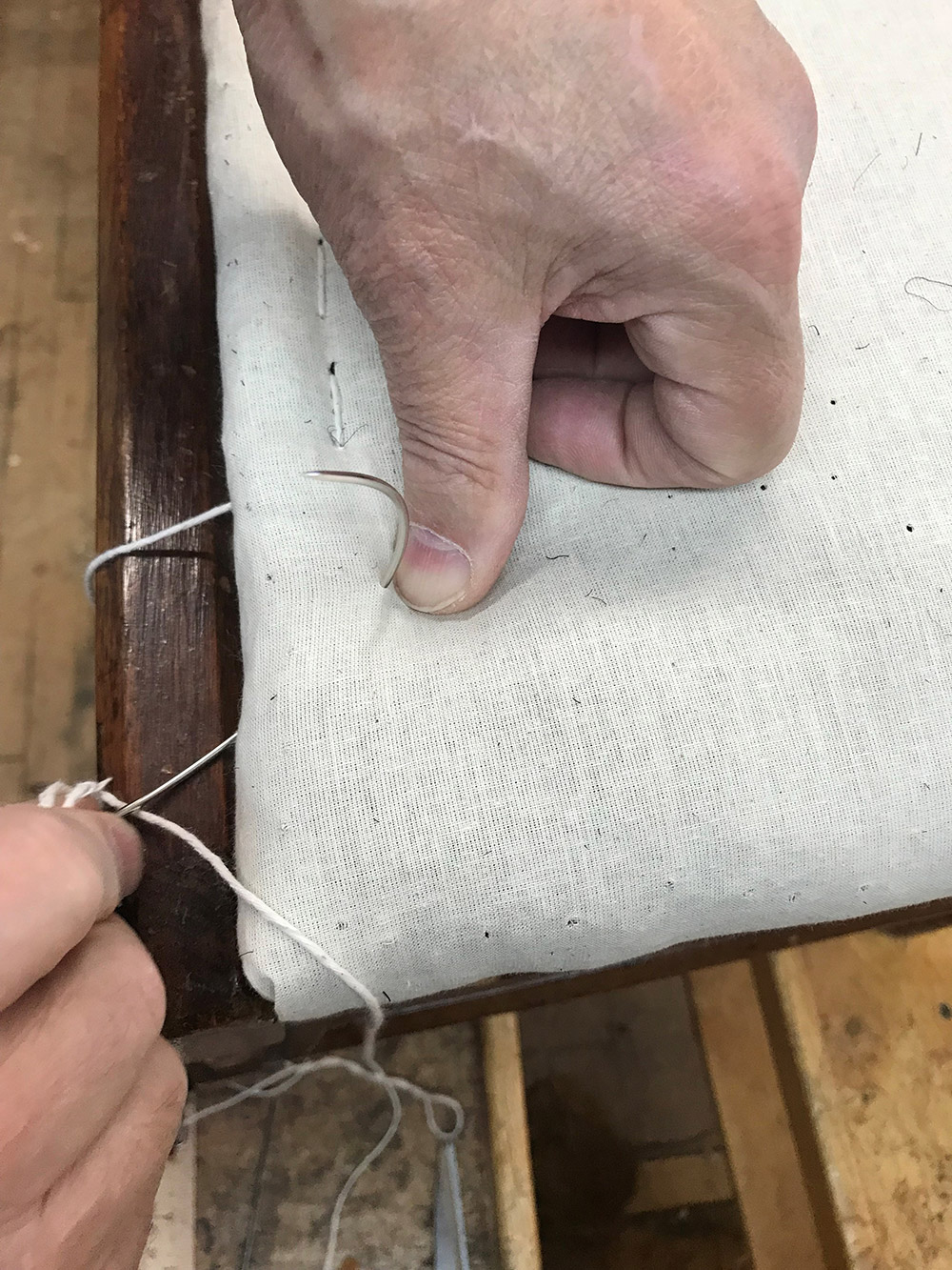 Curved round point needle penetrates muslin covered horse hair padding to create an edge roll.