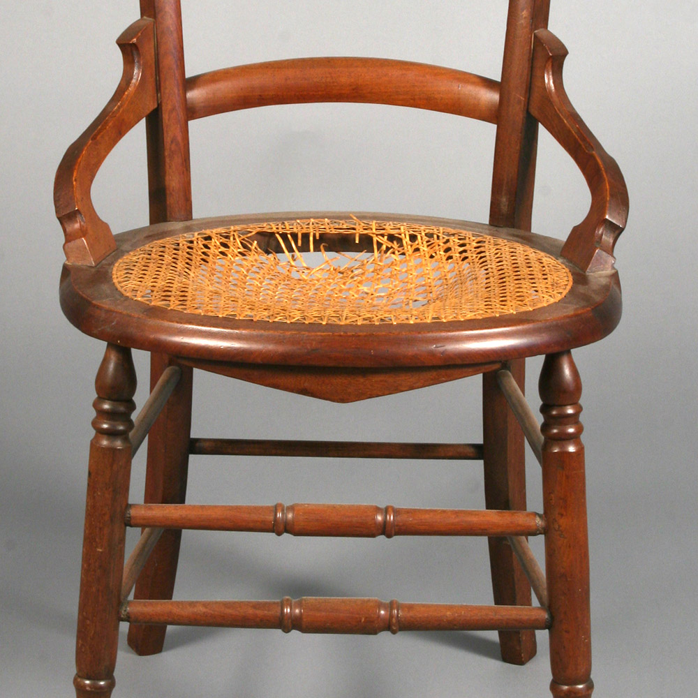 Caned chair marred by a sunken seat