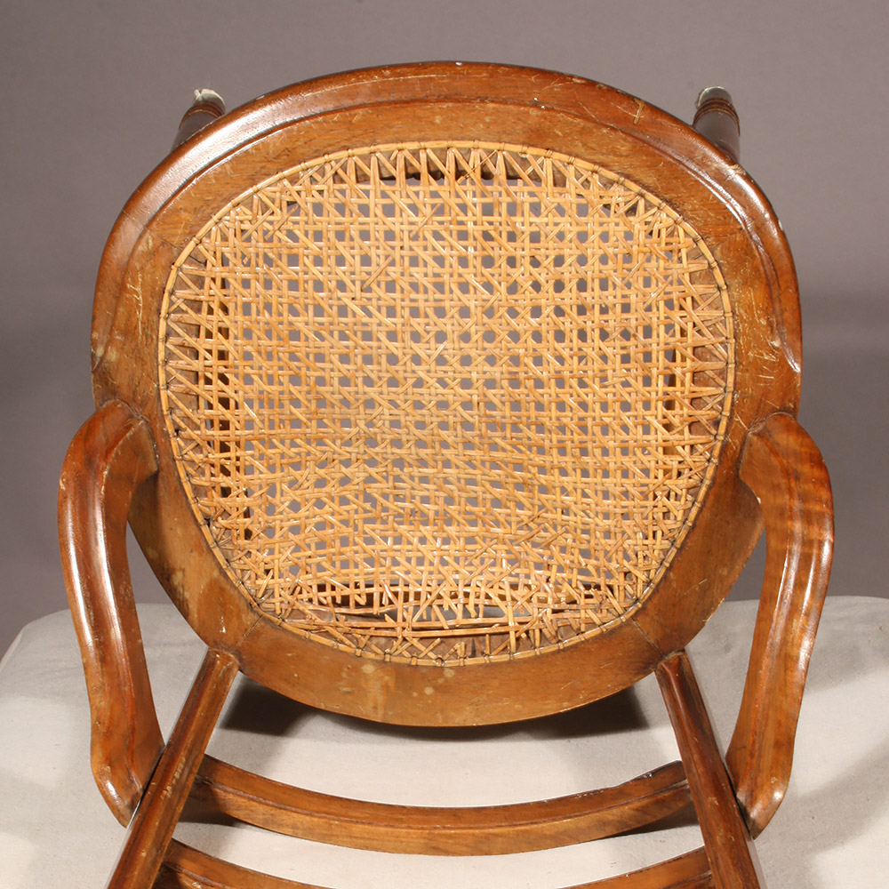 Caned seat with visible damage