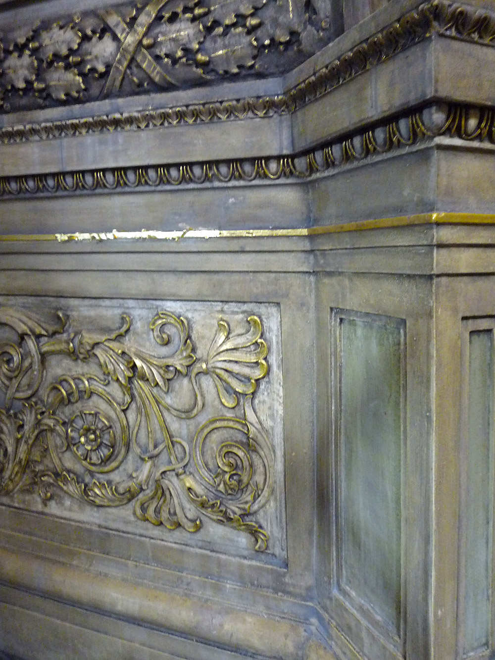 Gold leaf is applied to damaged areas of gilt plaster at Chicago's Blackstone Memorial Library