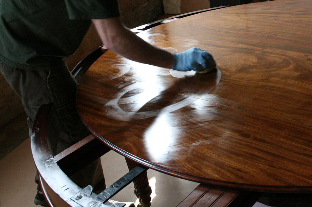 A French polishing pad is used to apply shellac in circular strokes with conservators working to quickly coat the table before the shellac sets