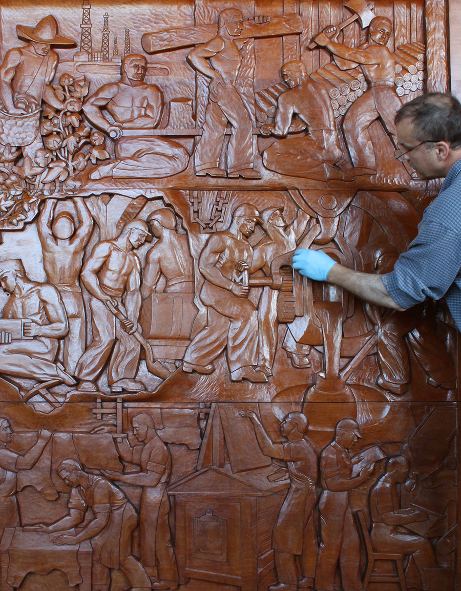 Photo:  The Evolution of the Book,     Wood Sculptural Relief by Peterpaul Ott, during conservation, final finish touch ups