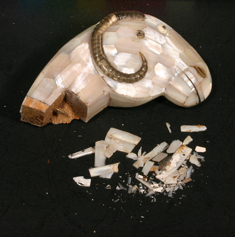 Detached ram's head with related damage to mother-of-pearl