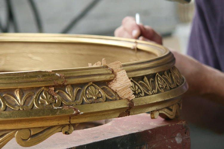 Detail of consolidating table apron. The table apron was detached in five sections with areas of wood loss, gesso, and gilding damage.