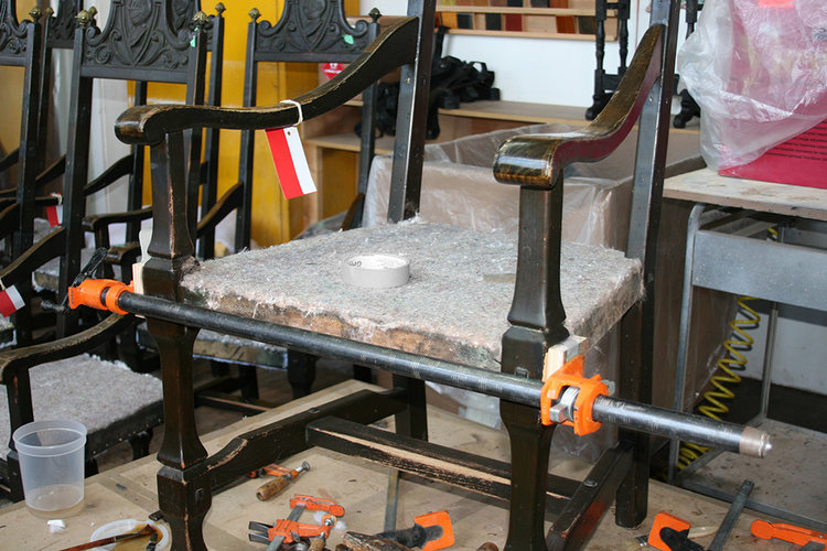 Clamping the wood frames after insertion of glue to re-stabilize the joints which loosened due to expansion and shrinkage cased by moisture exposure