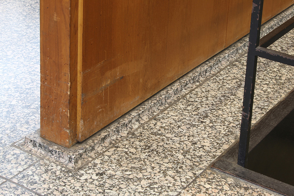Abrasions and water damage to veneered panels at the floor level | Photo courtesy of GSA