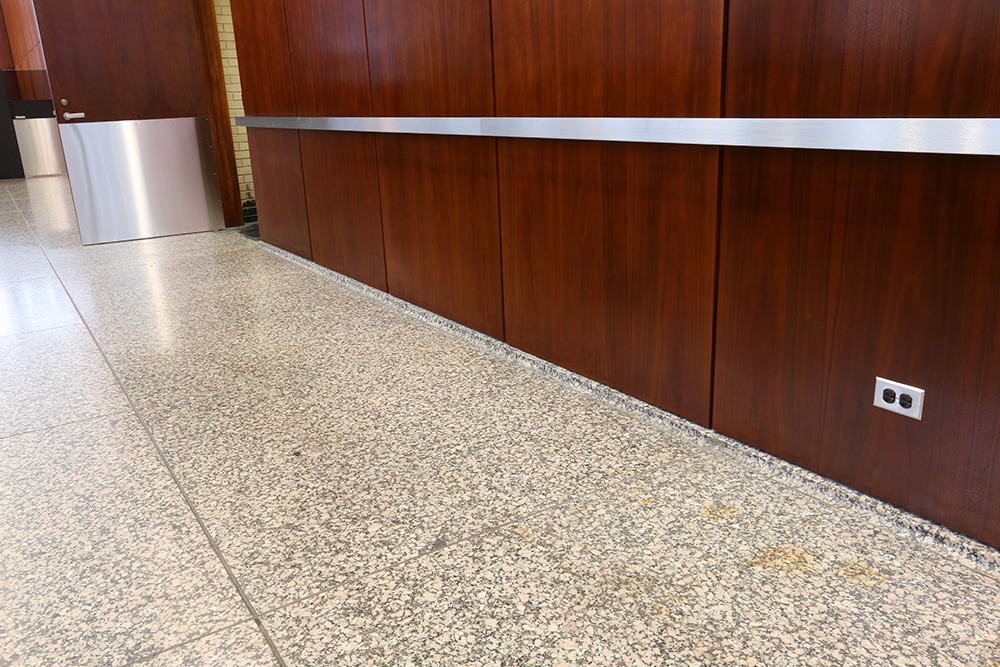 The same area after conservation and the installation of the stainless metal guard rail along the wall and panel protecting the door | Photo courtesy of GSA