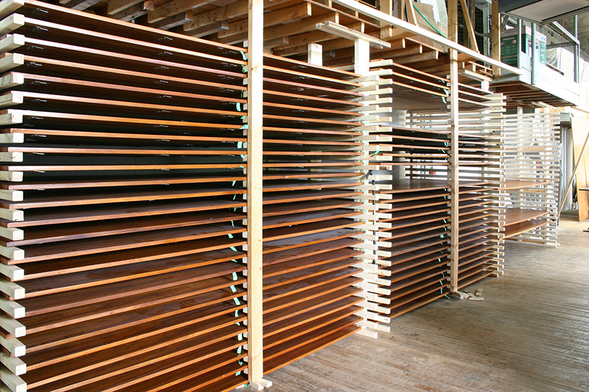 Veneered panels in custom drying racks where each coat of shellac was allowed to dry before the subsequent sanding and the next phase of finish application