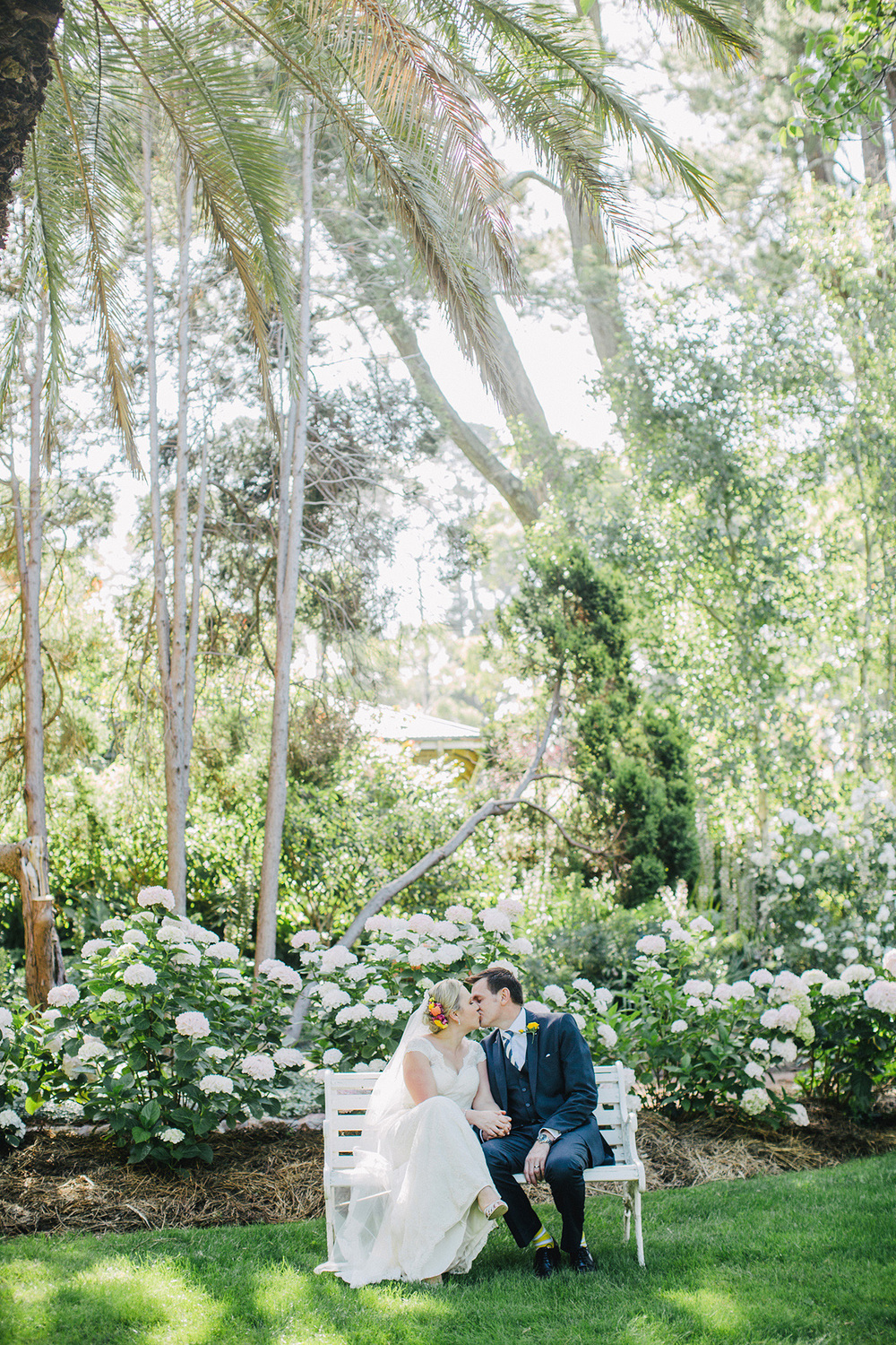 Hopewood House - Wedding Day Gallery - Lisa and Mark - At Dusk Photography -  Couple Kiss Garden Seat.jpeg