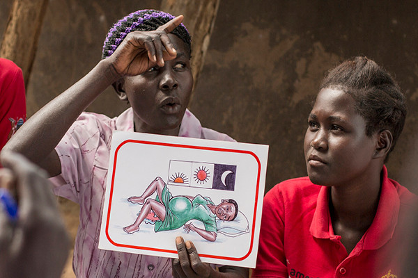 A women's health group meeting gather in Uganda, sharing potentially life-saving information using flash-cards