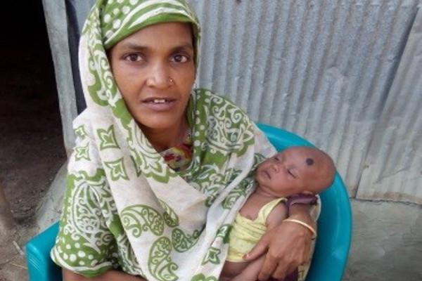 Shamoly holds her baby in the Shalpa Community, Bangladesh