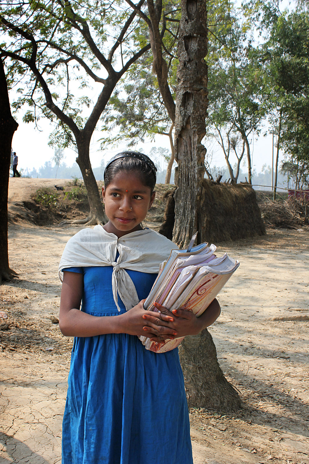 A young girl holds onto her books