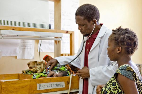 A doctor examines a newborn bab